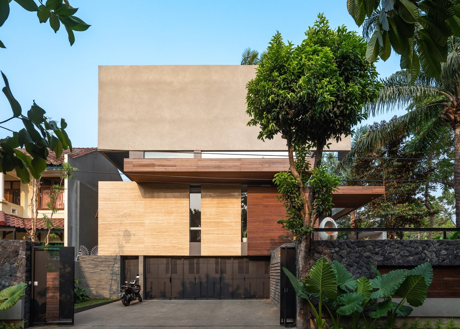 a multi-story home with a facade composed of several different materials, including both light and dark colored wood