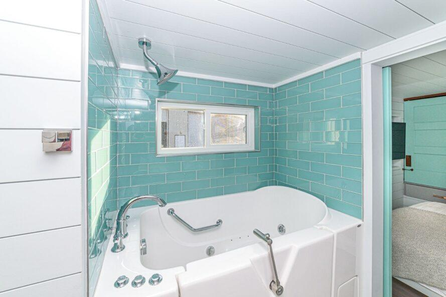 hot tub with teal tiled walls
