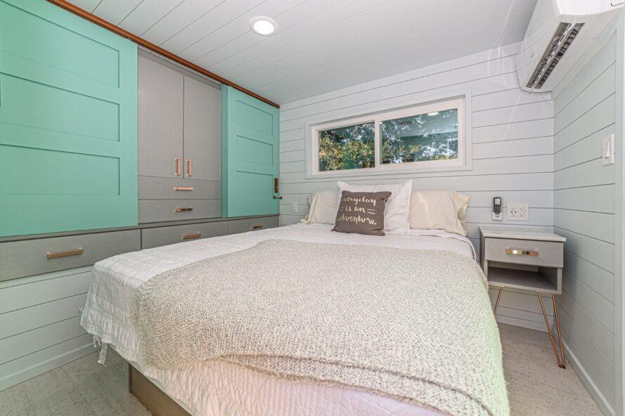 white bed beside gray and teal storage closet