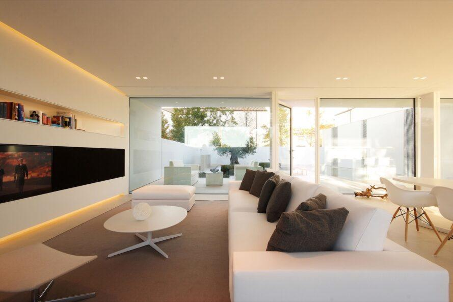 white sofa with gray pillows and a white coffee table