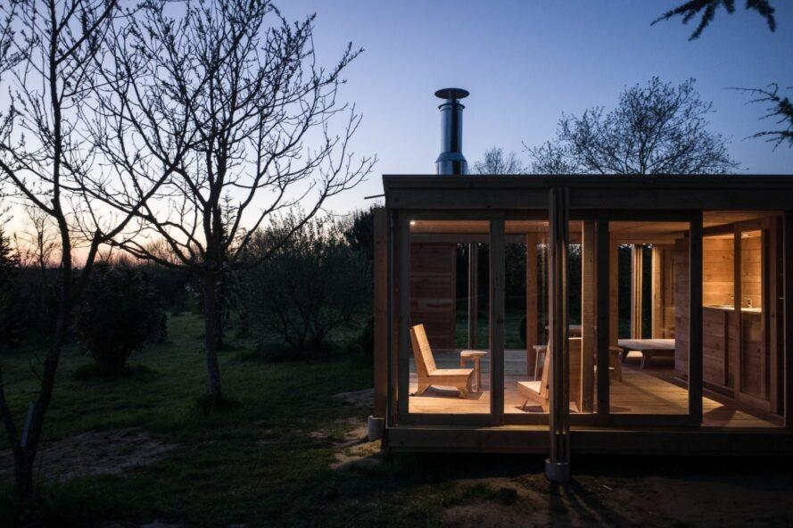 evening shot of tiny home with all glass walls