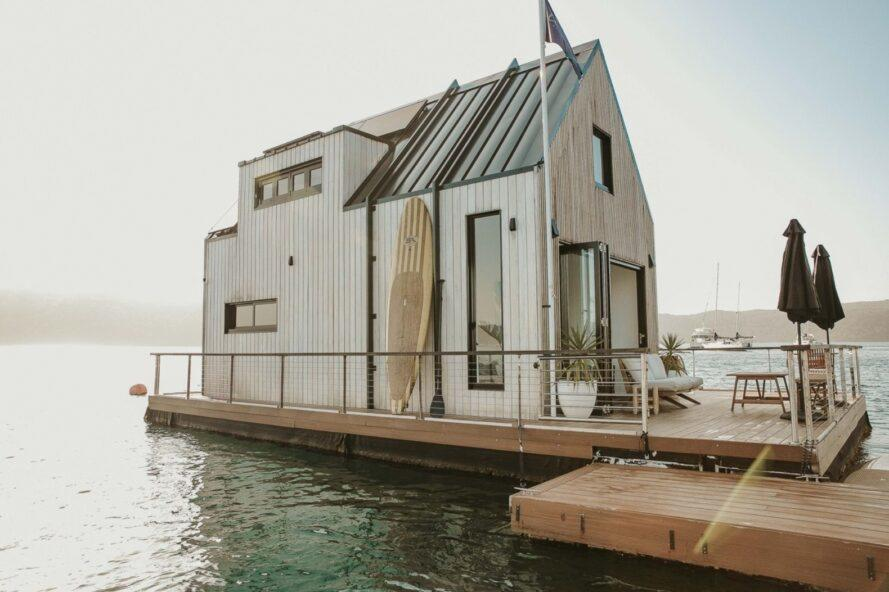 floating wood home with gabled roof and large patio