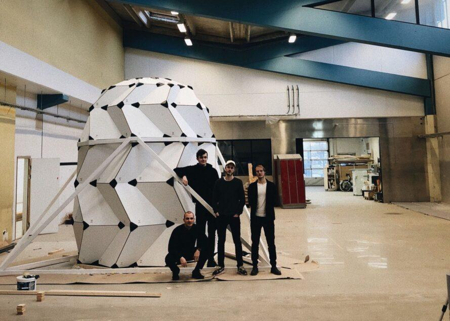 people building a full-size pod model with white panels