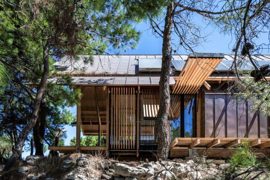 home on rocky landscape with open panels