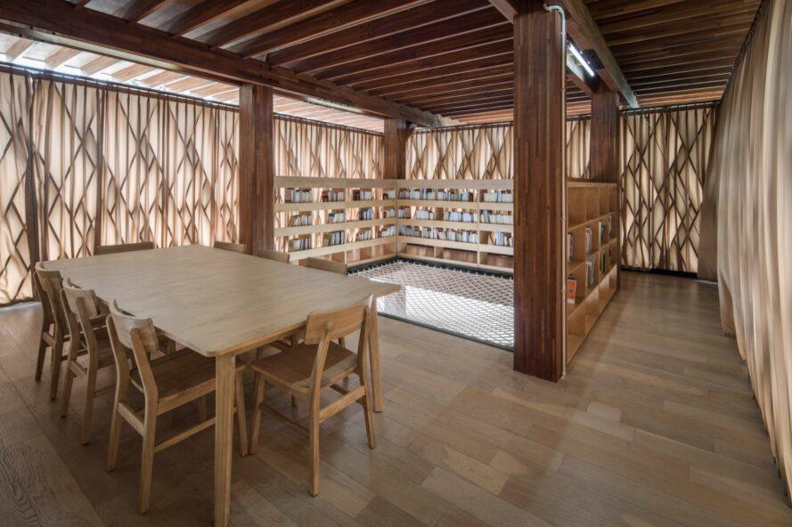interior of a wooden library with bookshelves, tables and chairs