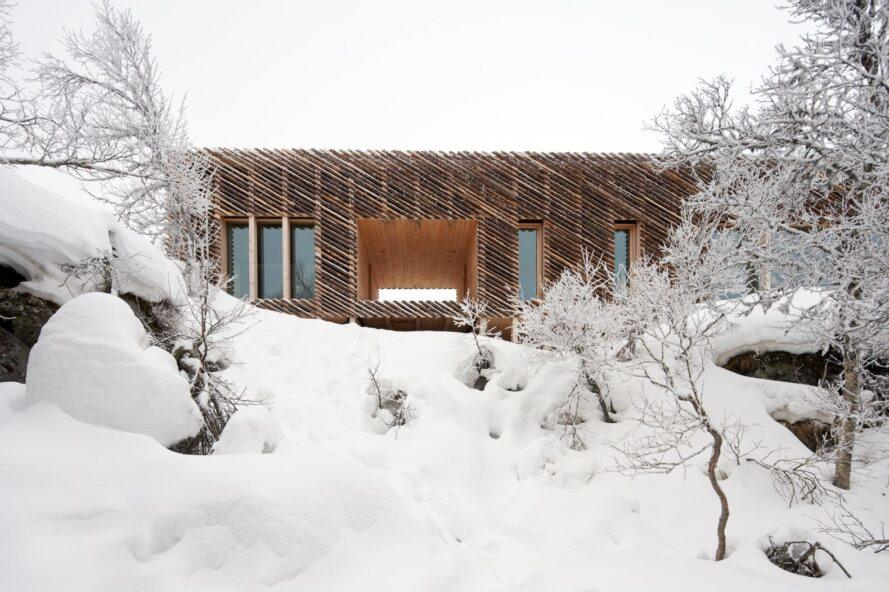 wooden cabin nearly covered in fluffy snow