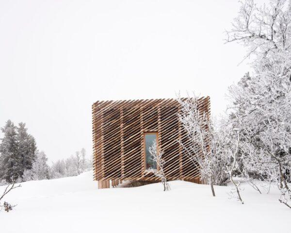 box-like wood cabin in snowy landscape