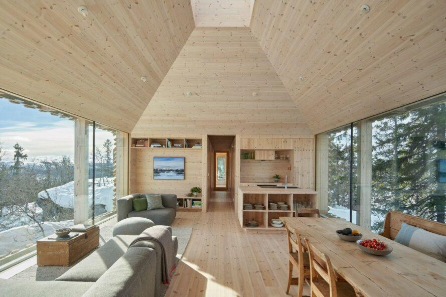 wood cabin interior with double-height ceiling, gray sofas and a wood dining table