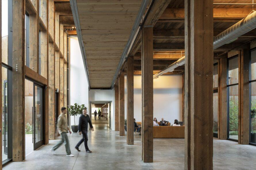 people walking into entrance with glass wall and wood support beams