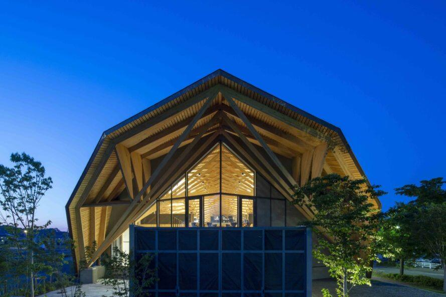 office building with geometric wood roof lit from within at night