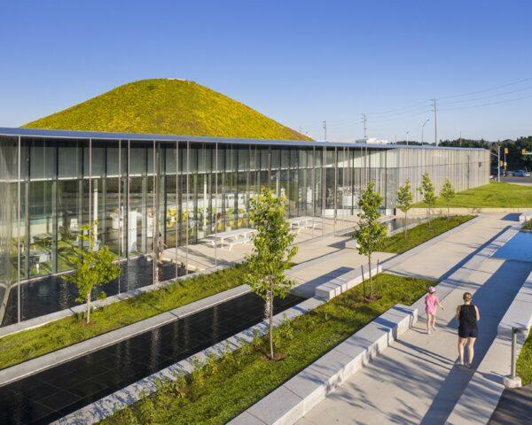glass building with a hilly green roof
