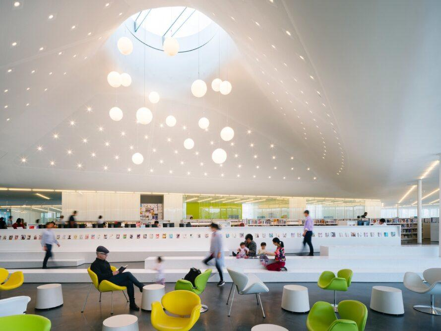 green, white and yellow chairs under a curvy ceiling with a round skylight
