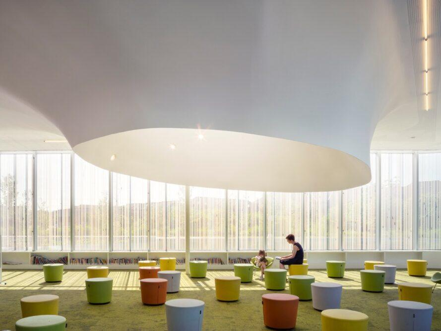 parent and child sitting on colorful stools in a glass building