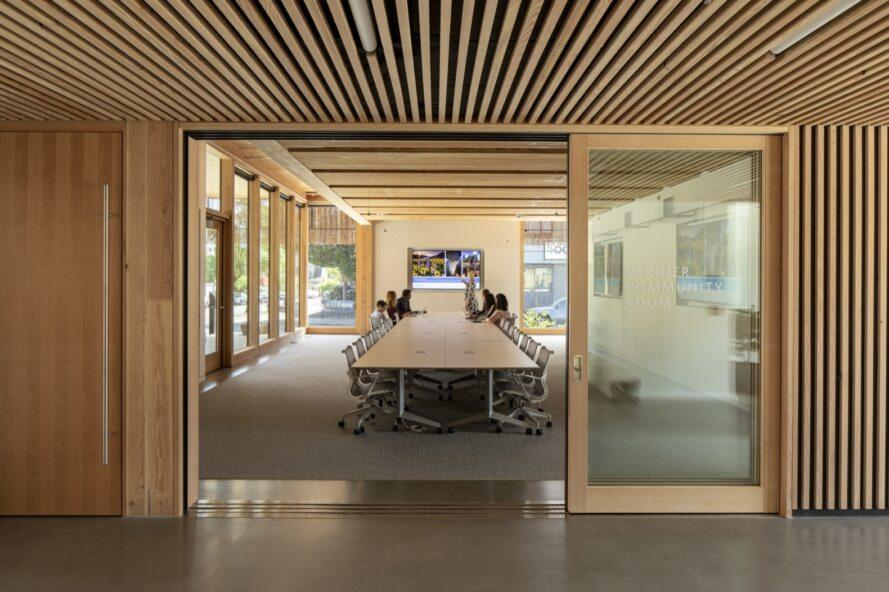 sliding glass door leading to large meeting room with long wood table and several windows