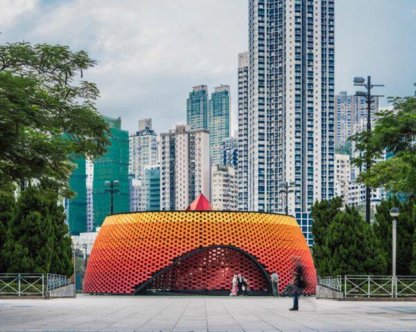 round orange and red pavilion made from recycled plastic bricks