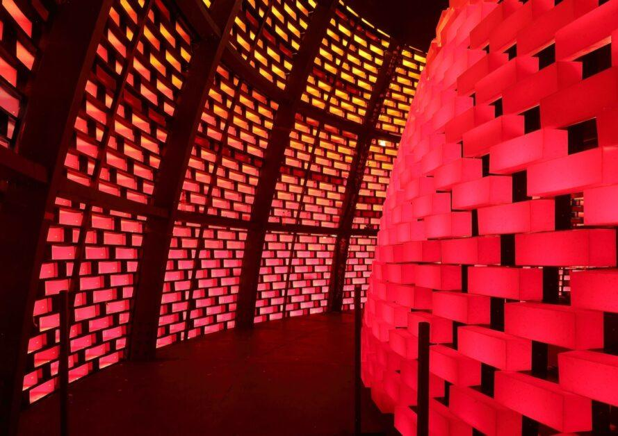 pavilion interior with walls of glowing red plastic bricks