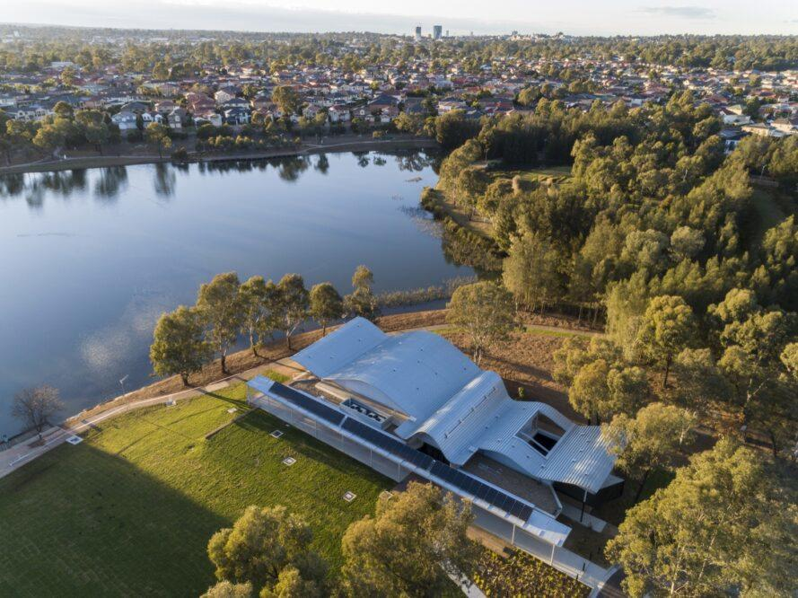 aerial view of lakeside community center with white wavy roof