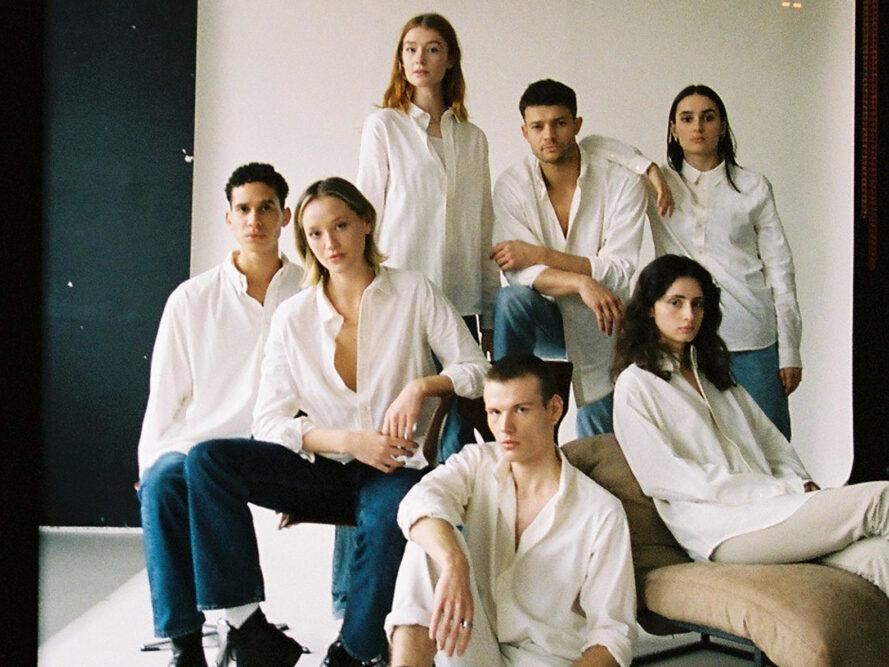 several models in white button-down shirts and jeans