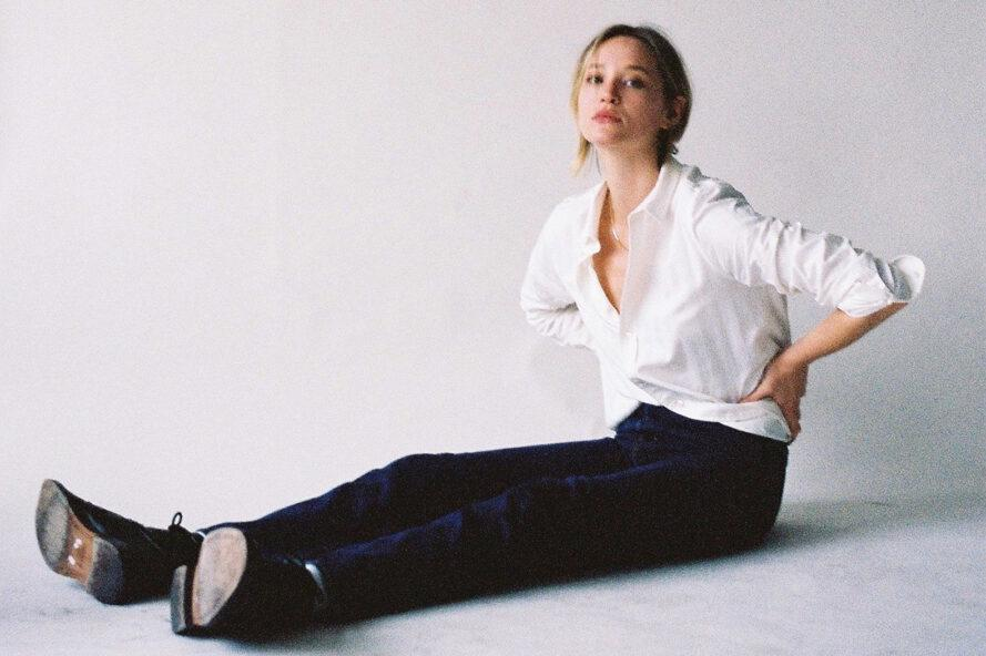 person sitting on floor wearing dark jeans and a white tailored shirt