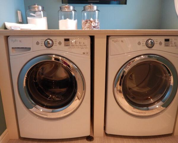 energy-efficient washer and dryer with homemade laundry detergent in glass jar on top