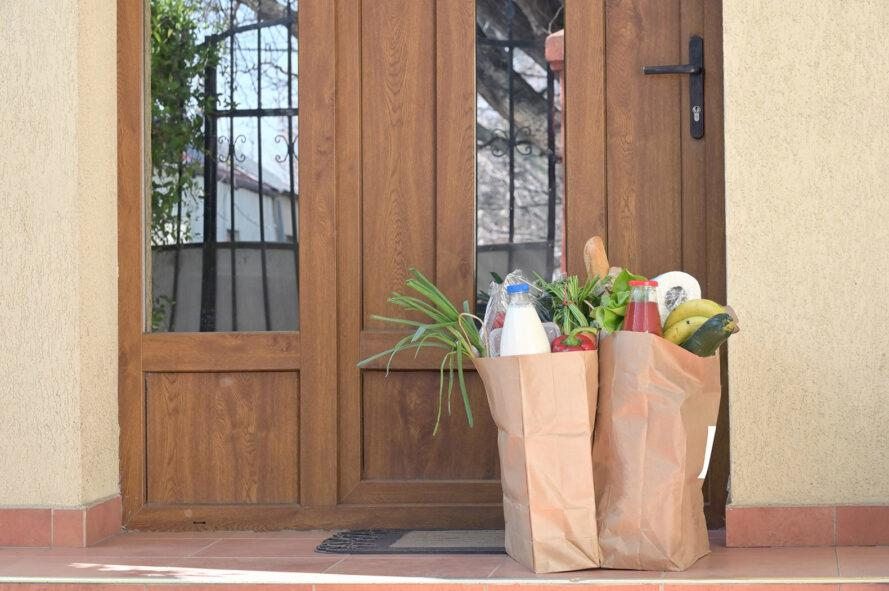two paper bags full of groceries on a front porch