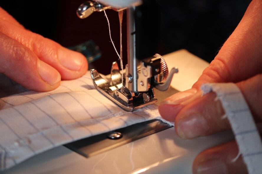person using sewing machine to make fabric mask