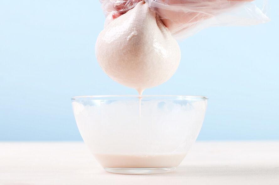person straining milk from almond pulp