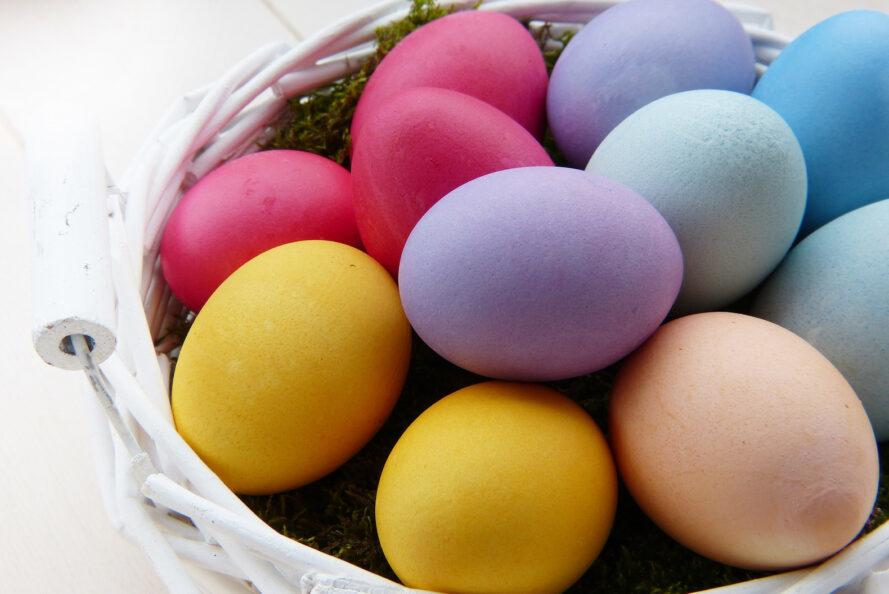 purple, blue and yellow Easter eggs in a white wicker basket