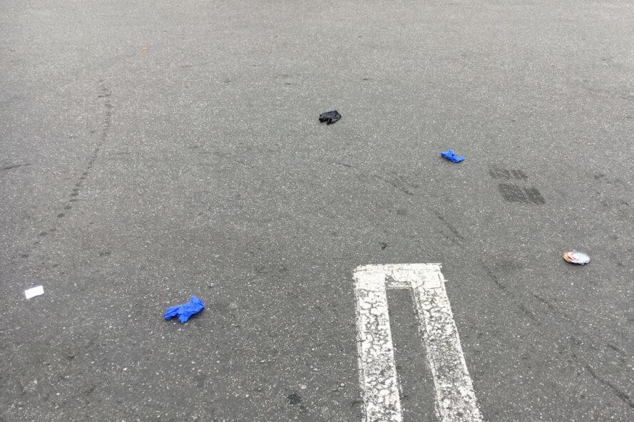 blue and black latex gloves littered in a parking lot