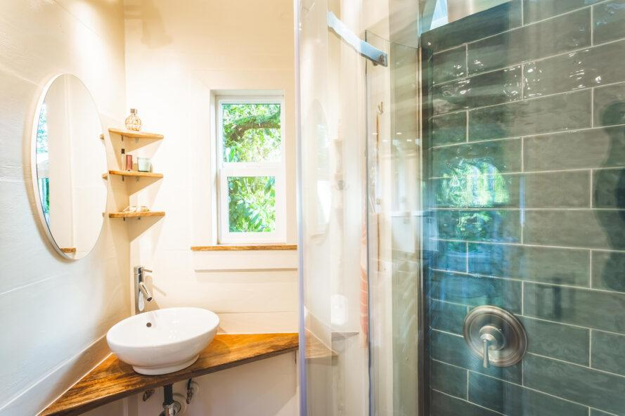 a bathroom with a corner sink and shelves, and a blue-tiled shower