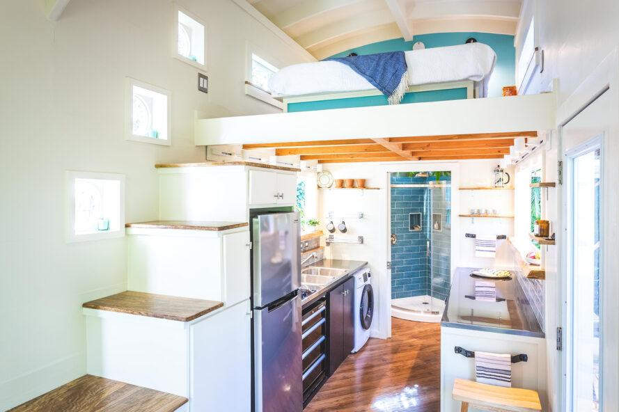 interior of a tiny home, featuring white and blue accents. a fridge and kitchen area are tucked underneath a staircase leading to a bedroom loft