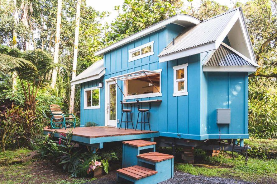 a blue tiny home with three steps leading up to it via a wood porch. the home is surrounded by tropical greenery