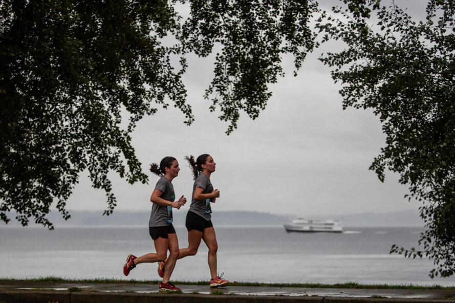 two people running beside waterfront with boats