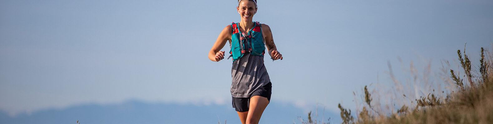 person running and smiling with ocean and mountains in background