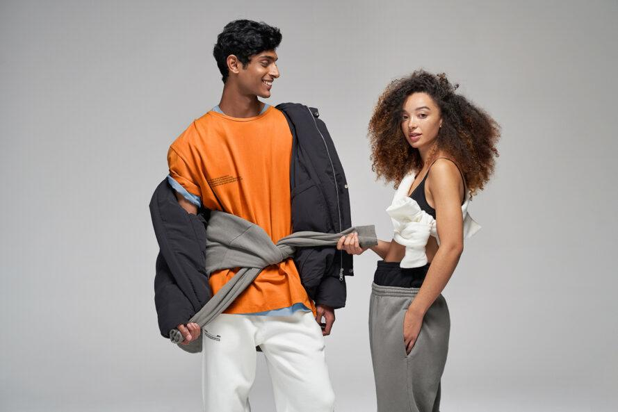 two people wearing gray, black, white and orange T-shirts and tracksuits