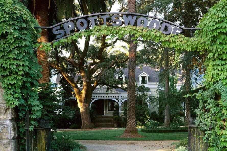"a metal archway covered in green ivy and reading ""Spottswoode"" stands in front of the front lawn with trees that obscure an estate building"