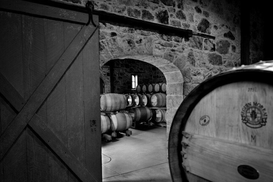 black and white image of a stone wine cellar full of wine barrels