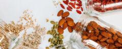 jars of seeds and nuts spilling onto white background