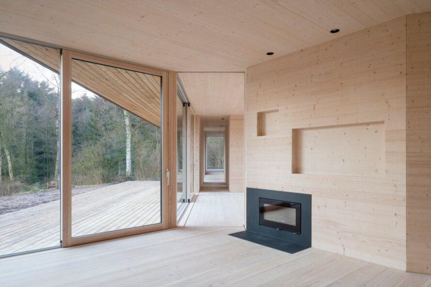 light wood-lined home with small fireplace and one glass wall