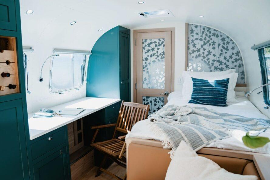 white bed beside a small white desk inside an Airstream