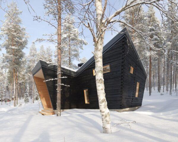 an angular black wood building in the middle of a snowy forest