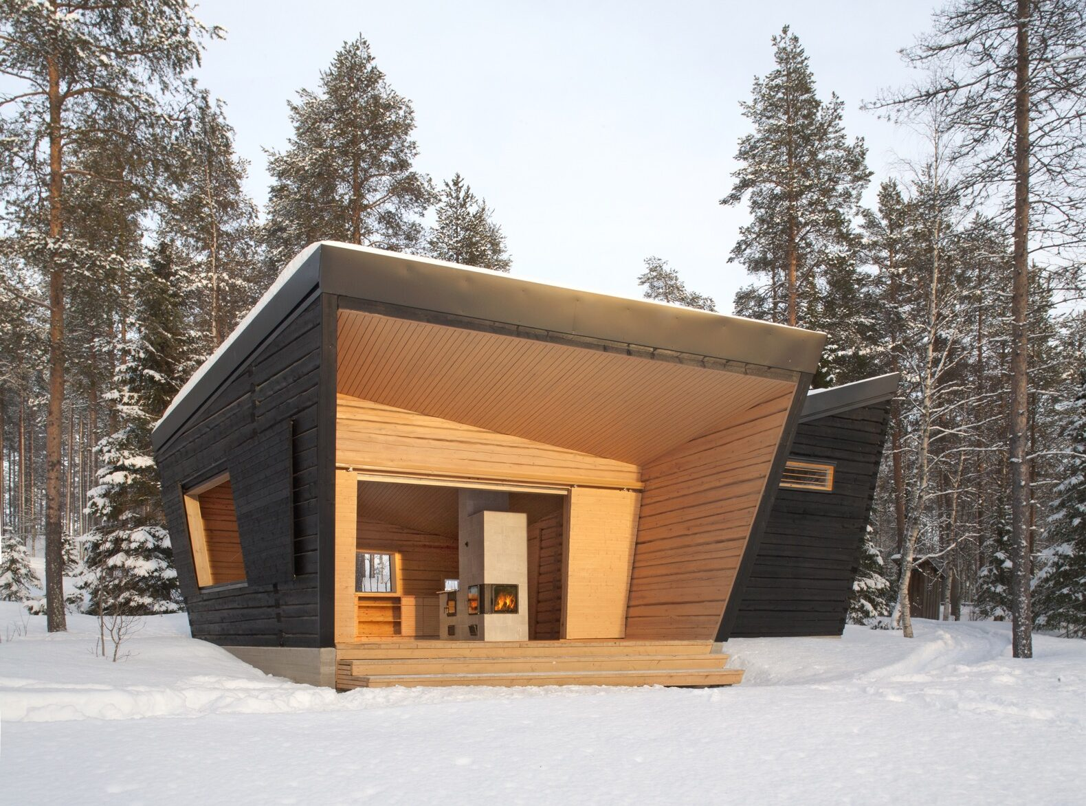 an angular building with a black wood facadel, light wood accents and an open entrance area in the middle of a snowy forest