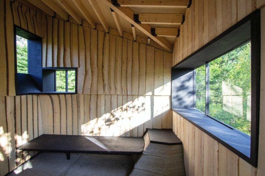 small wood cabin interior with benches along the walls