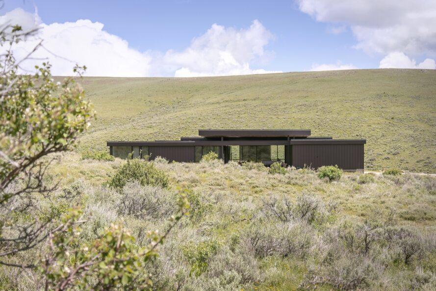elongated black home on rolling green hills