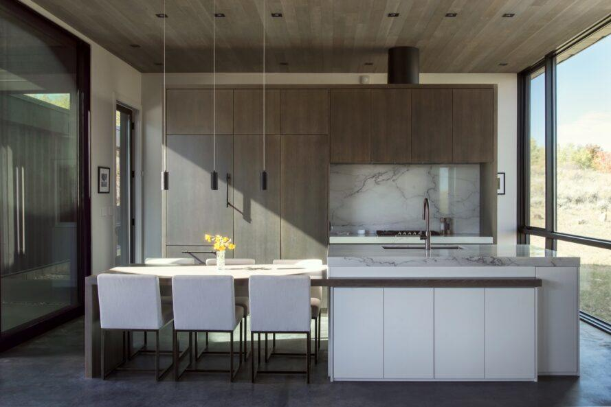 long white kitchen island with white dining chairs