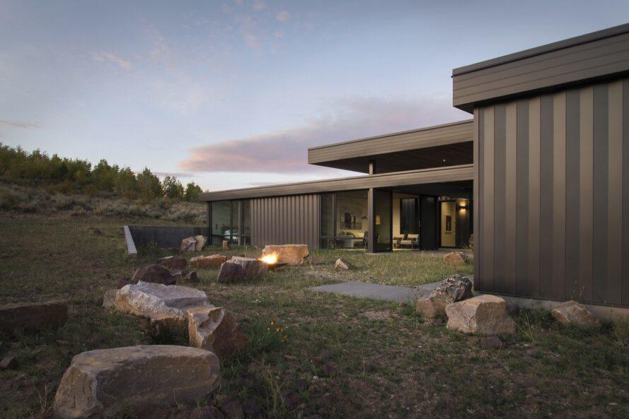 dark home with large backyard with rock seats and a fire pit