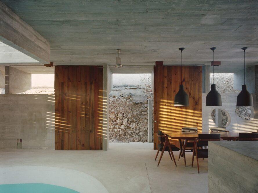 wood dining table and chairs near a pool in a concrete room