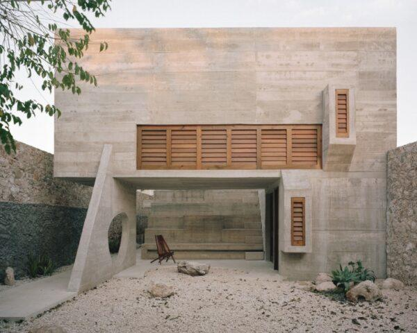concrete home with wood shutters over the windows