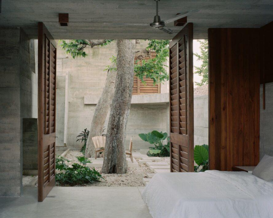 wood doors opening to a small courtyard with trees