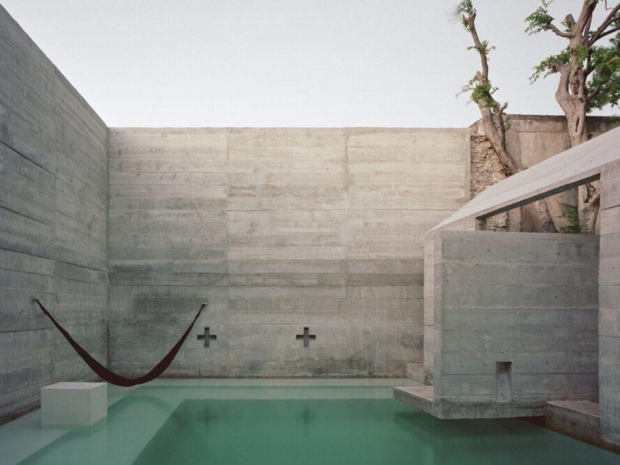 hammock above a pool enclosed by concrete walls